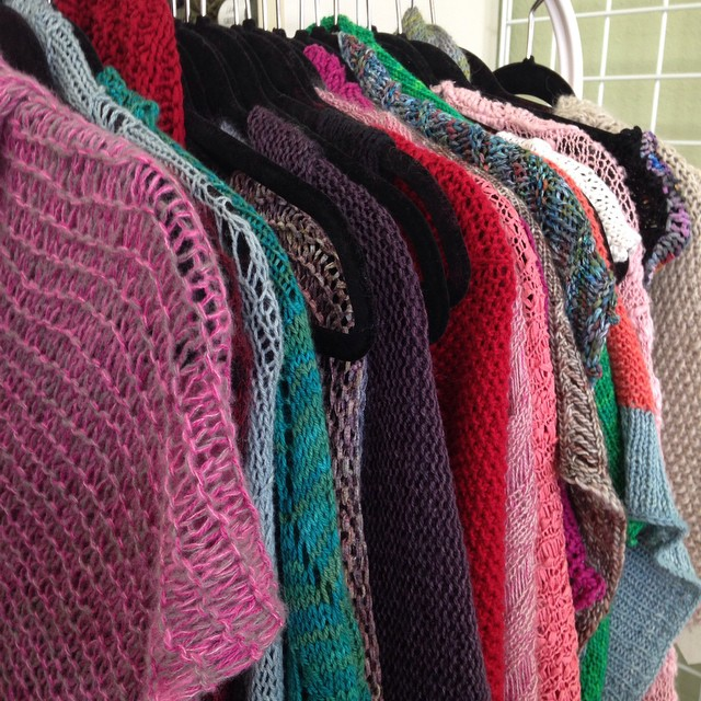 Look at all the pretty shawls I saw today at @unwind_yarn. #knitting #twistedstitches